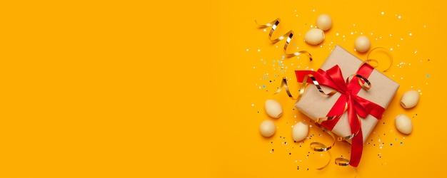 Gouden verfraaide eieren van pasen met cadeaus of dozen met rode bogen en confettien Premium Foto