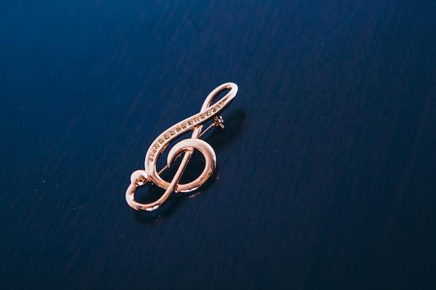Gouden viool op een donkere. verfraaiing, broche. . muzikale symbolen, geïsoleerde objecten, sieraden, sieraden Premium Foto