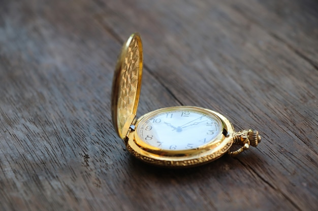 Gouden zakhorloge klassiek ontwerphorloge 10.10 uur gezet op houten lijstachtergrond Premium Foto
