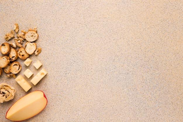 Goudse kaas en emmentaler met walnoot; sneetje brood en rauwe pasta op de achtergrond Gratis Foto
