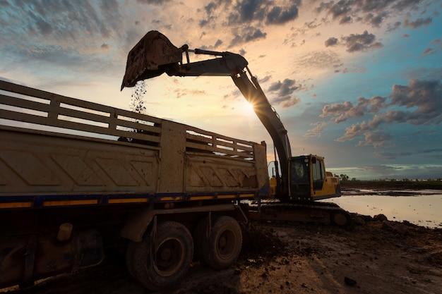 Graafmachine in zandbak tijdens grondverzetwerkzaamheden voor het vullen van een kiepwagen met steen en grond voor het vullen van een nieuw wegenbouwproject voor commerciële ontwikkeling Premium Foto