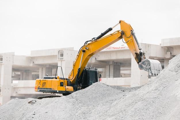 Graafmachine werkt op de bouwplaats rock verplaatsen voor het bouwen van tolweg Premium Foto