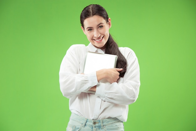 Graag computer concept. aantrekkelijk vrouwelijk halflang voorportret, trendy groene muur. jonge emotionele mooie vrouw. menselijke emoties, gezichtsuitdrukking Gratis Foto