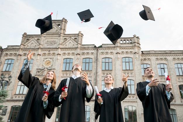 Graduatieconcept met student die hoeden in lucht werpen Premium Foto