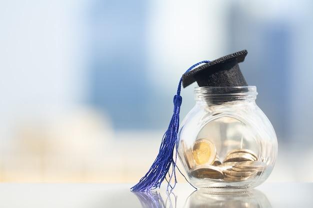 Graduatiehoed met blauwe leeswijzer bovenop glaskruik die met muntstukken op moderne stadsachtergrond wordt gevuld Premium Foto