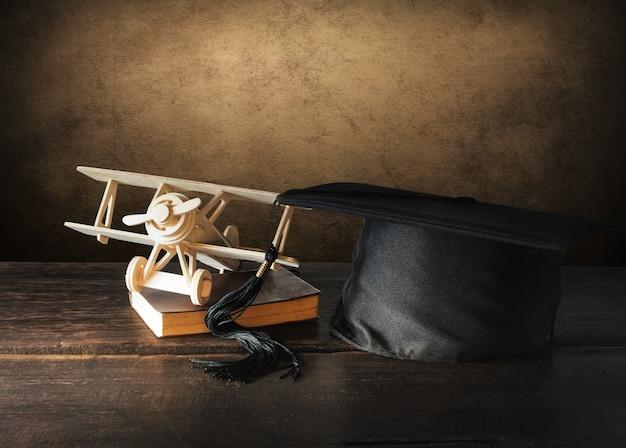 Graduatiekap, hoed met houten stuk speelgoed vliegtuig op houten lijst Premium Foto