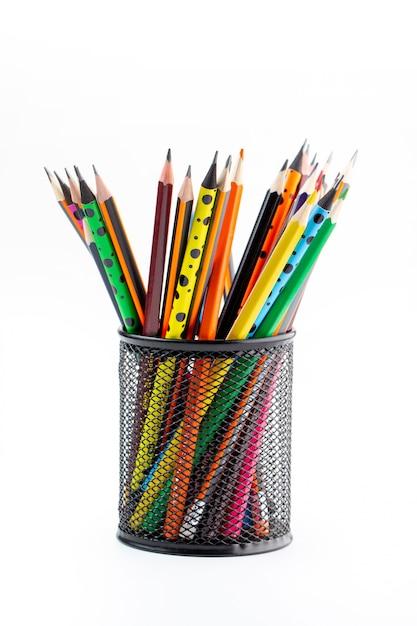 Grafiet tekenpotloden helder bekleed binnen zwarte mand op wit bureau Gratis Foto