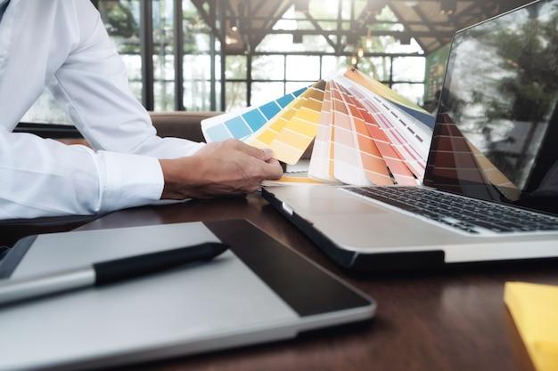Grafisch ontwerp en kleurstalen en pennen op een bureau. architectonische tekening met werkgereedschap en accessoires. Gratis Foto