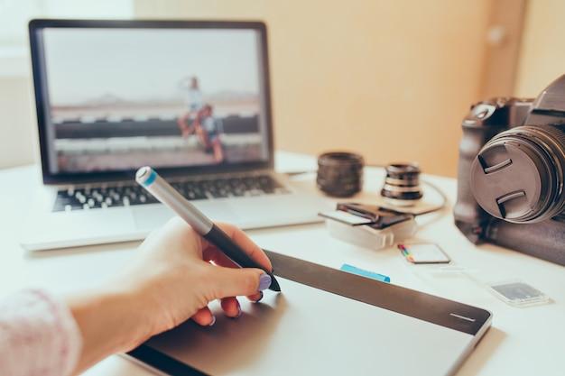 Grafisch ontwerper werkt met interactieve pendisplay, digitale tekentablet en pen op een computer. vloeiende tracking-opname met mooie lensflare met achtergrondverlichting. Gratis Foto
