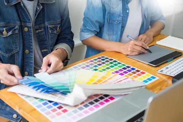 Grafisch ontwerpersteam die aan webontwerp werken die kleurenmonsters gebruiken die kunstwerk bewerken die tablet en een naald gebruiken bij bureaus in bezig creatief bureau. Premium Foto