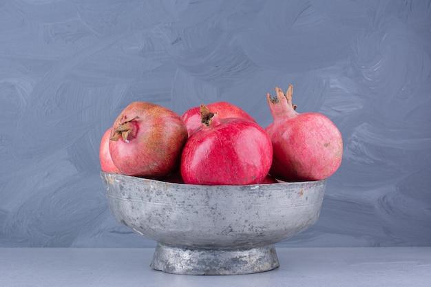 Granaatappels in een metalen vaas op marmeren achtergrond. Gratis Foto