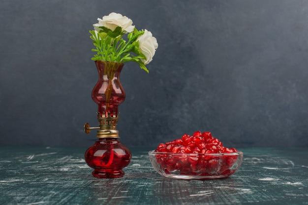 Granaatappelzaden en witte bloemen in vaas. Gratis Foto