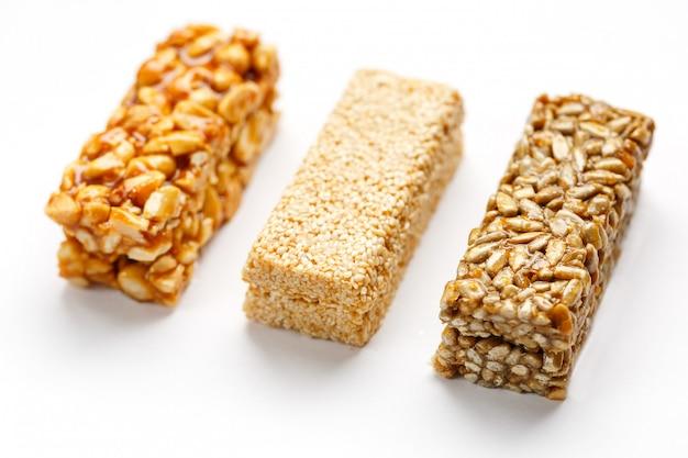 Granola reep met pinda's, sesam en zaden op een rij. bovenaanzicht drie verschillende staven, isoleren Premium Foto