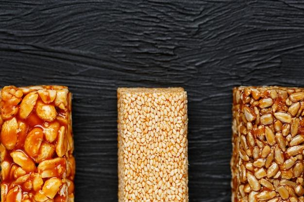 Granola reep met pinda's, sesam en zonnebloempitten op een snijplank op een donkere stenen tafel. uitzicht van boven. drie verschillende repen Premium Foto