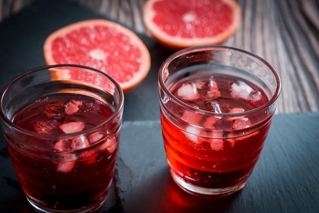 Grapefruitlimonadeglas met ijsblokjes en druppeltjes. Premium Foto