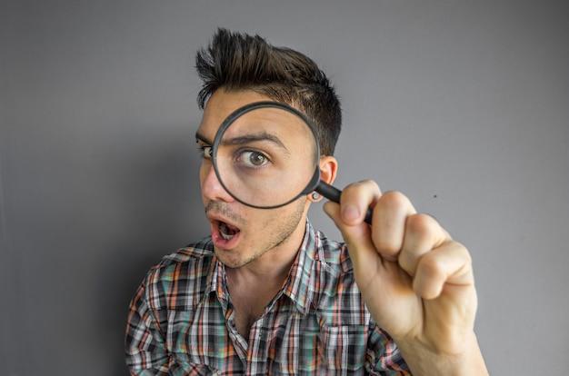 Grappig beeld van een knappe man spelen met een vergrootglas Premium Foto