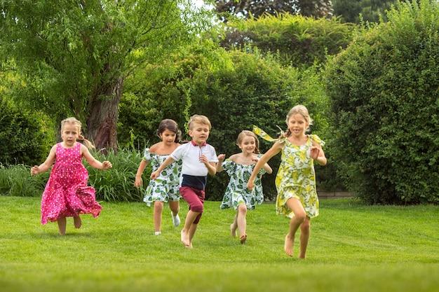 Grappig begint. kindermode concept. groep tienerjongens en meisjes die bij park lopen Gratis Foto