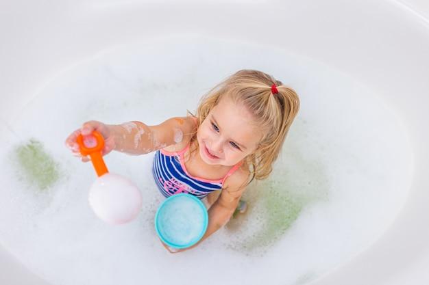Grappig blond meisje dat schuimbad in mooie badkamers neemt. hygiëne van kinderen. shampoo, haarbehandeling en zeep voor kinderen. Premium Foto