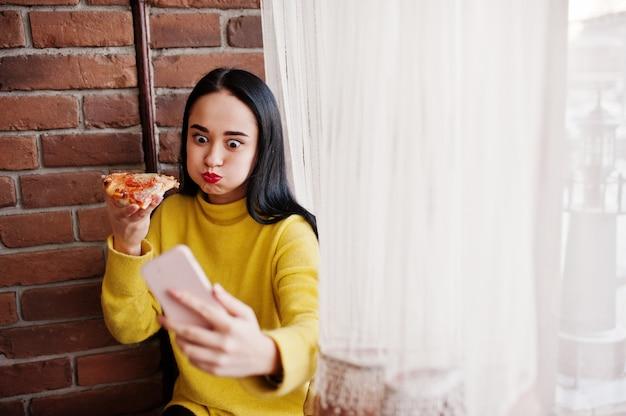 Grappig donkerbruin meisje in gele pizza eten bij restaurant en selfie die maken. Premium Foto