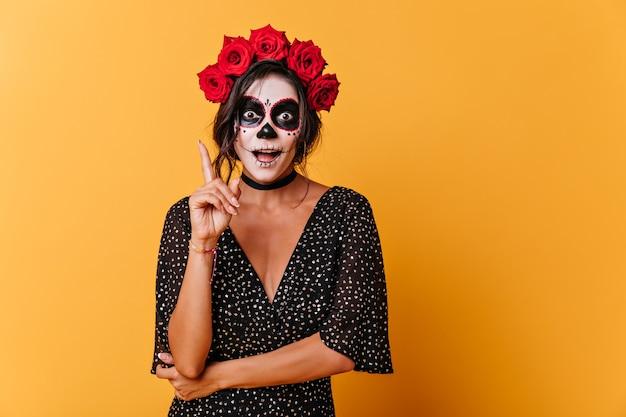 Grappig gebruind meisje met geverfd gezicht herinnerde zich een interessante gedachte. portret van vrouw met rozen op haar hoofd in oranje studio. Gratis Foto