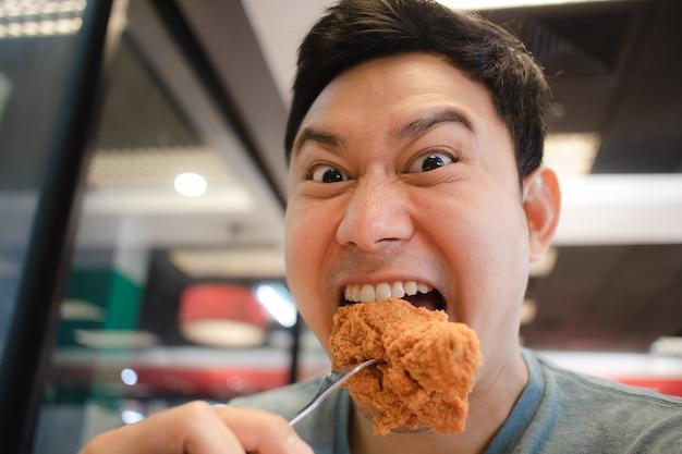 Grappig gezicht aziatische man eet gebakken kip. Premium Foto