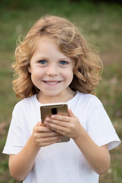 Grappig kind dat met lang haar mobiel houdt Premium Foto