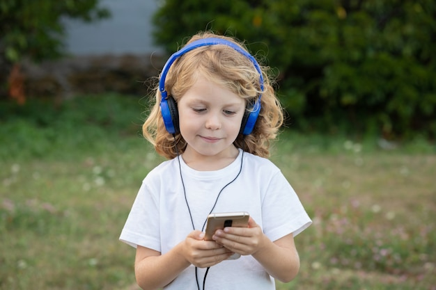 Grappig kind met lang haar luisteren muziek met blauwe hadphones en een mobiel Premium Foto