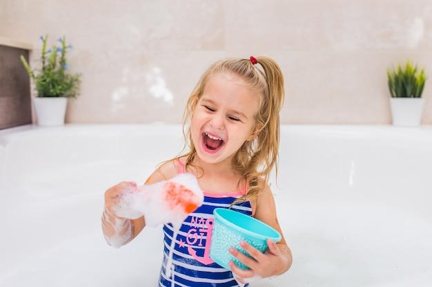 Grappig klein blondemeisje die schuimbad in mooie badkamers nemen. hygiëne van kinderen. shampoo, haarbehandeling en zeep voor kinderen. copyspace. Premium Foto