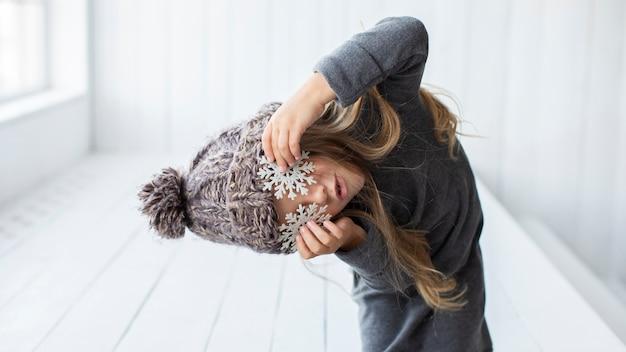 Grappig meisje dat haar ogen bedekt met sneeuwvlokken Gratis Foto
