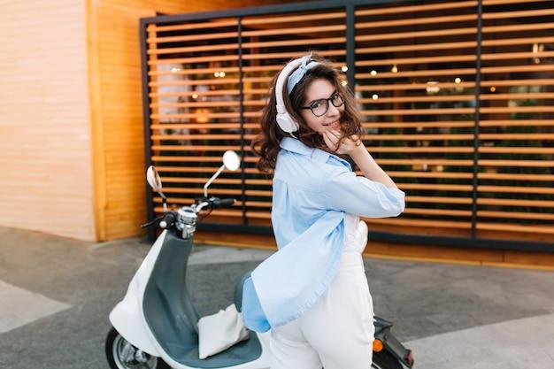 Grappig meisje in blauw oversized overhemd speels poseren op straat genieten van muziek in witte koptelefoon Gratis Foto