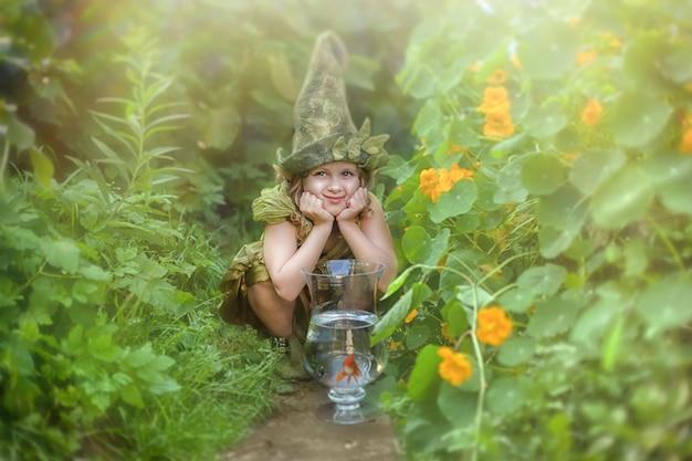 Grappig meisje in een kabouterhoed en een kostuum in een groene tuin. Premium Foto