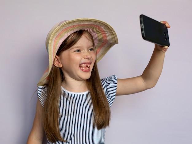 Grappig meisje maakt selfie door smartphone Premium Foto