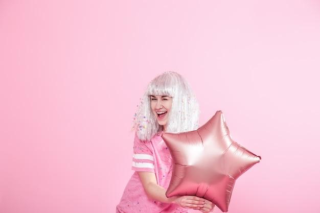 Grappig meisje met zilveren haren geeft een glimlach en emotie op roze achtergrond. jonge vrouw of tiener meisje met ballonnen en confetti Gratis Foto