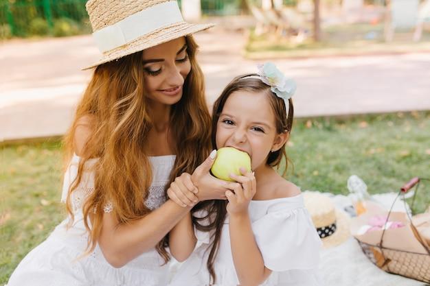 Grappig meisje neemt een hap van een grote groene appel die haar mooie moeder vasthoudt. outdoor portret van lachende jonge vrouw in elegante hoed dochter voeden met lekker fruit in zonnige dag. Gratis Foto