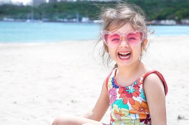 Grappig meisje poseren in zonnebril spelen met zand op het strand. zomerentertainment en recreatie. Gratis Foto