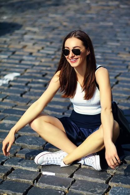 Grappig modieus sexy het glimlachen mooi jong vrouwenmodel in de doekzitting van de zomer heldere hipster in de straat Gratis Foto