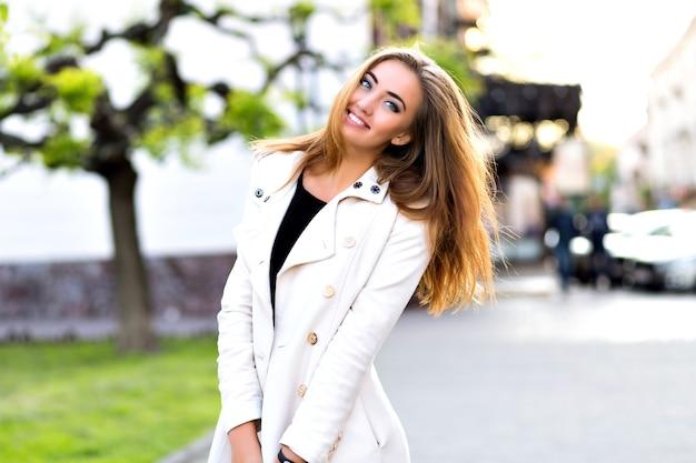Grappig portret van gelukkig blond meisje, grappige gezichten maken en tong tonen op straat, herfsttijd, rust in de stad. Gratis Foto