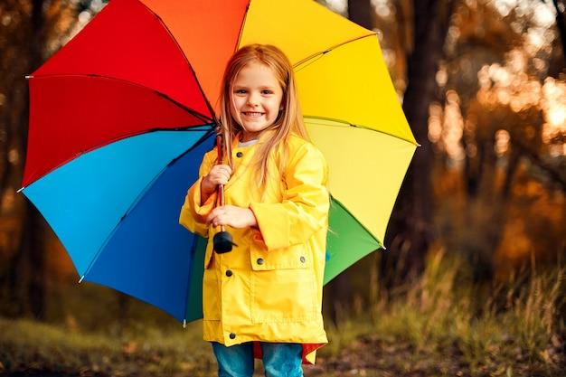 Grappig schattig peuter meisje dragen waterdichte jas met kleurrijke paraplu Premium Foto