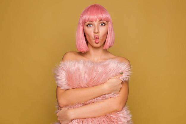 Grappig schot van jonge aantrekkelijke roze harige vrouw met kort trendy kapsel gezichten maken terwijl poseren over mosterdmuur met schattig harig kussen in haar handen Gratis Foto