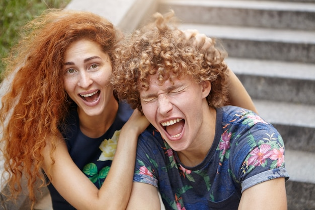 Grappig sproeterig vrouwtje met roodachtig borstelig haar scratcing hoofd van haar vriend die ogen sluit en mond opent. paar verliefd luid lachen Gratis Foto