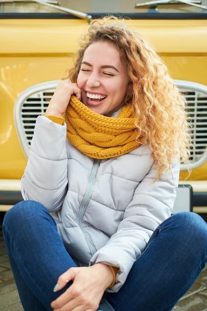 Grappige aantrekkelijke roodharige krullende vrouw die voorzijde van gele auto situeert en met gesloten ogen glimlacht Premium Foto