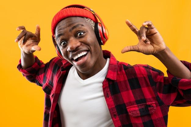 Grappige afrikaanse zwarte man stijlvol gekleed met een grimas op zijn gezicht luistert naar muziek met een koptelefoon op een gele studio achtergrond Premium Foto