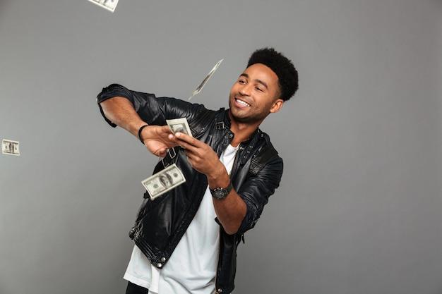 Grappige afro amerikaanse rijke man die dollarsbankbiljetten verspreiden Gratis Foto