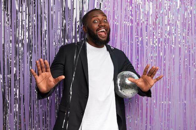 Grappige afro-man in stijlvol pak, houdt glanzende discobal vast, danst en zingt op muziek, viert een afscheidsfeestje met vrienden, heft palmen op, is in een hoge geest, geïsoleerd over versierde paarse muur Gratis Foto