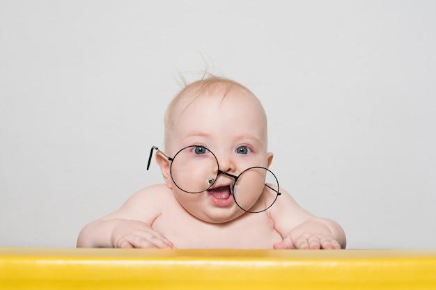 Grappige baby in grote ronde glazen aan de tafel Premium Foto