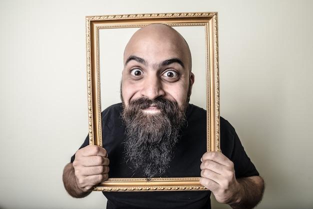 Grappige bebaarde man met gouden frame Premium Foto