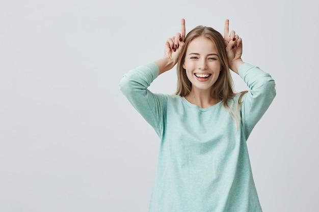 Grappige blonde vrouw die breed houdend vingers boven hoofd glimlacht. hoorns gebaar Gratis Foto