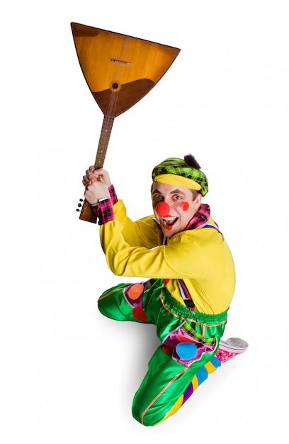 Grappige clown met een balalaika die op een wit wordt geïsoleerd Premium Foto