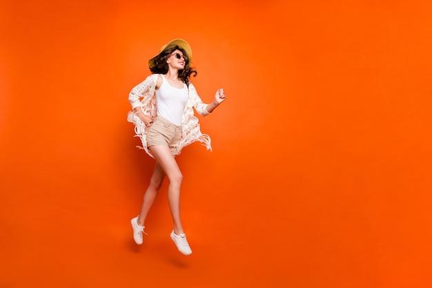 Grappige dame hoog springen, wandelen, stijlvolle zonnehoed dragen vintage stijlvolle trendy cape shorts. Premium Foto