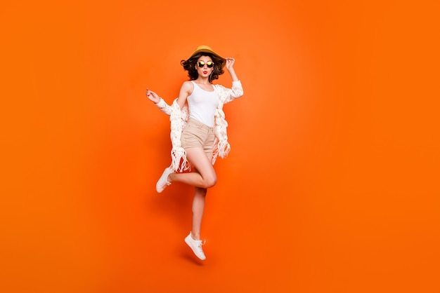 Grappige dame zomertijd hoog springen genieten resort uitzicht kusjes verzenden dragen zonnehoed witte kanten strandmantel korte broek. Premium Foto